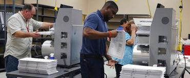 Election workers in Broward County feed ballots into machines
