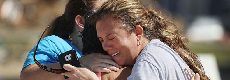 Neighbors hug Thursday in Mexico Beach. Their homes were heavily damaged by the storm.
