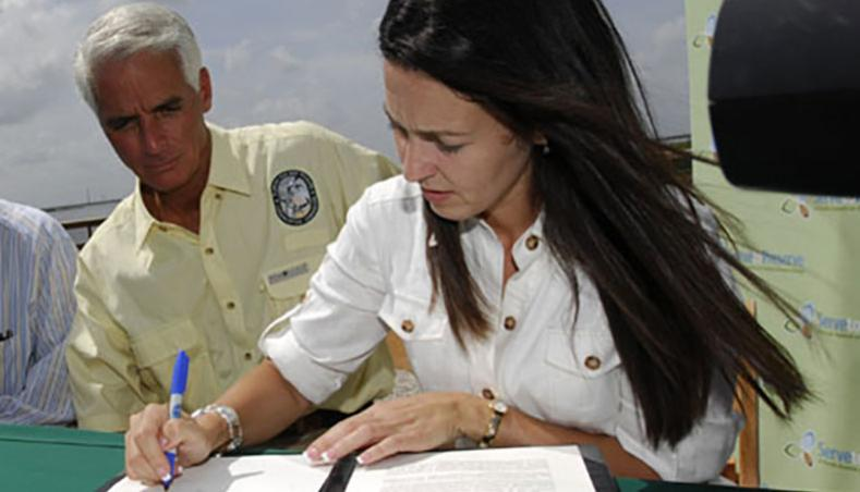 "Gov. Charlie Crist stands as official witness as Shannon Estenoz, SFWMD vice chair, signs the U.S. Sugar deal's ""Statement of Principles."""